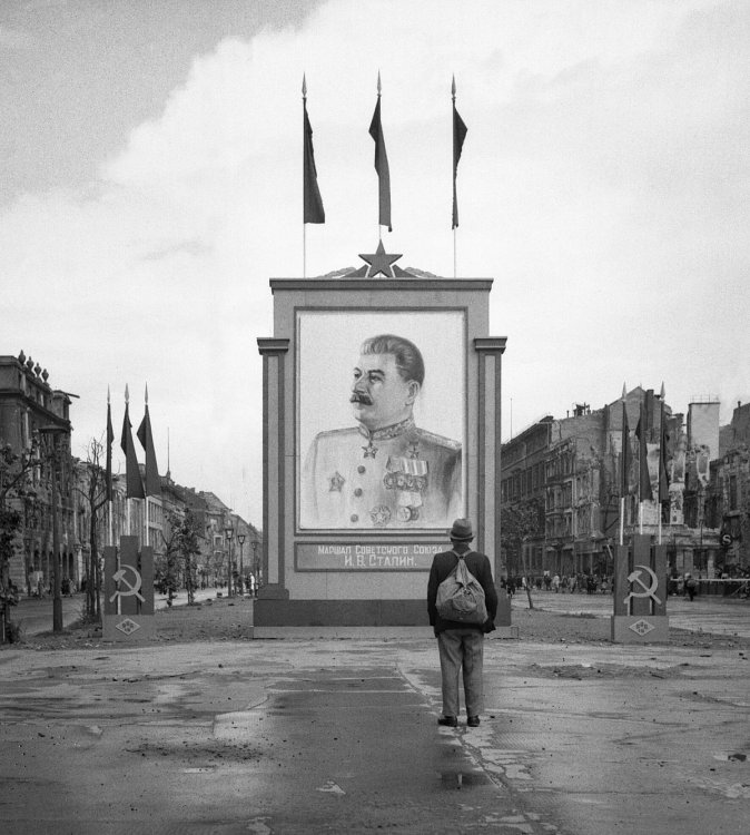 1200px-A_German_civilian_looks_at_a_large_poster_portrait_of_Stalin_on_the_Unter-den-Linden_in_Berlin,_3_June_1945._BU8572.jpg