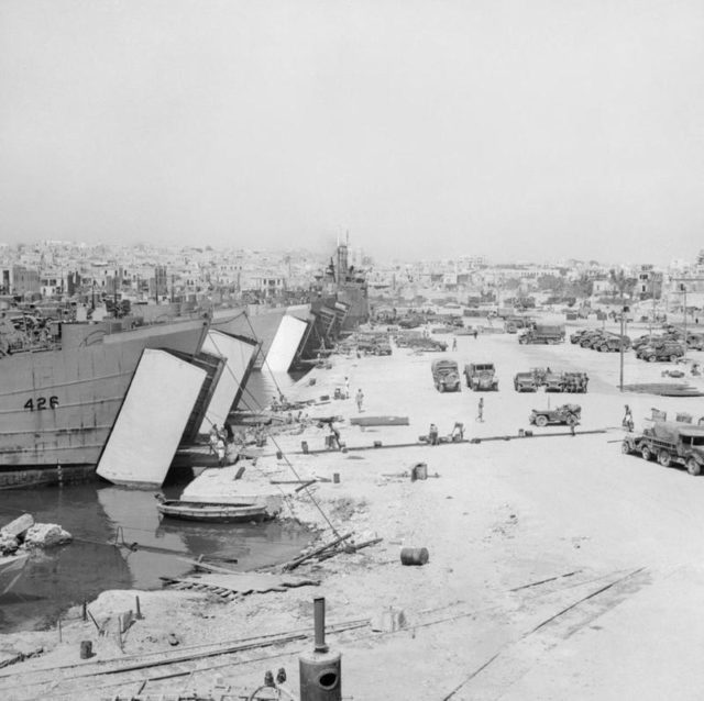 view-of-the-dockside-of-sousse-harbour-tunisia-landing-craft-are-loaded-with-vehicles-and-equipped-in-preparation-for-the-invasion-iwm-na-3938.jpg