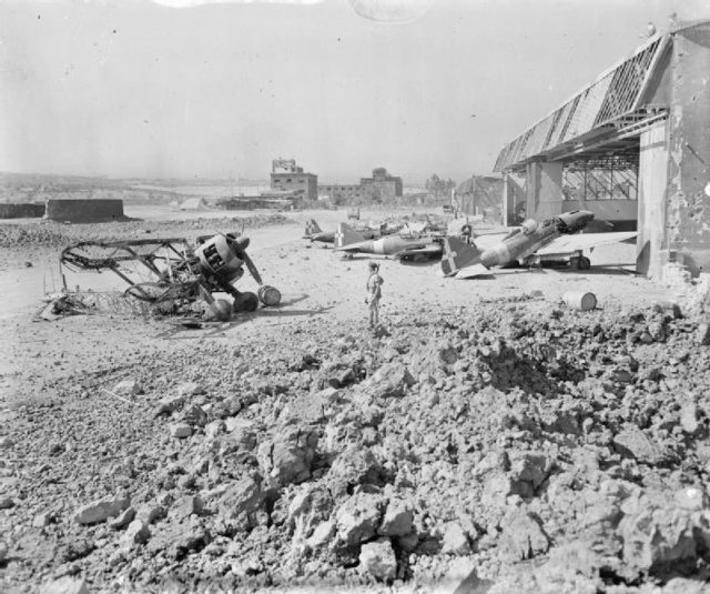 wrecked-and-damaged-italian-fighters-outside-bomb-shattered-hangars-at-catania-sicily-under-the-scrutiny-of-an-airman-shortly-after-the-occupation-of-the-airfield-by-the-raf-iwm-cna-1352.jpg